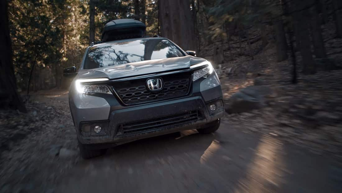 Front view of the 2019 Honda Passport Elite in Lunar Silver Metallic, with accessory roof box, driving on dirt road in forest.