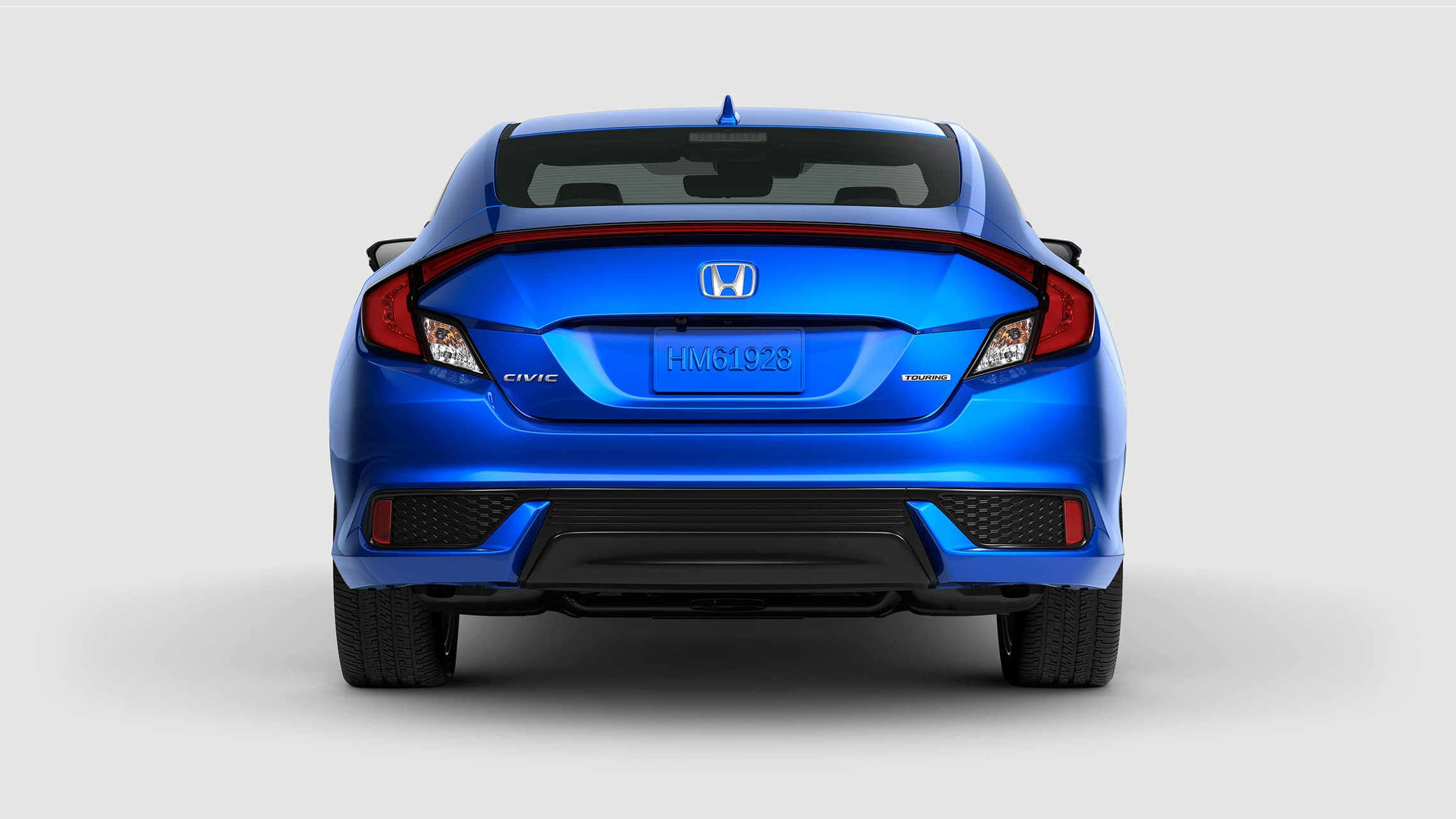 Rear view of the 2020 Honda Civic Touring Coupe in Aegean Blue Metallic.