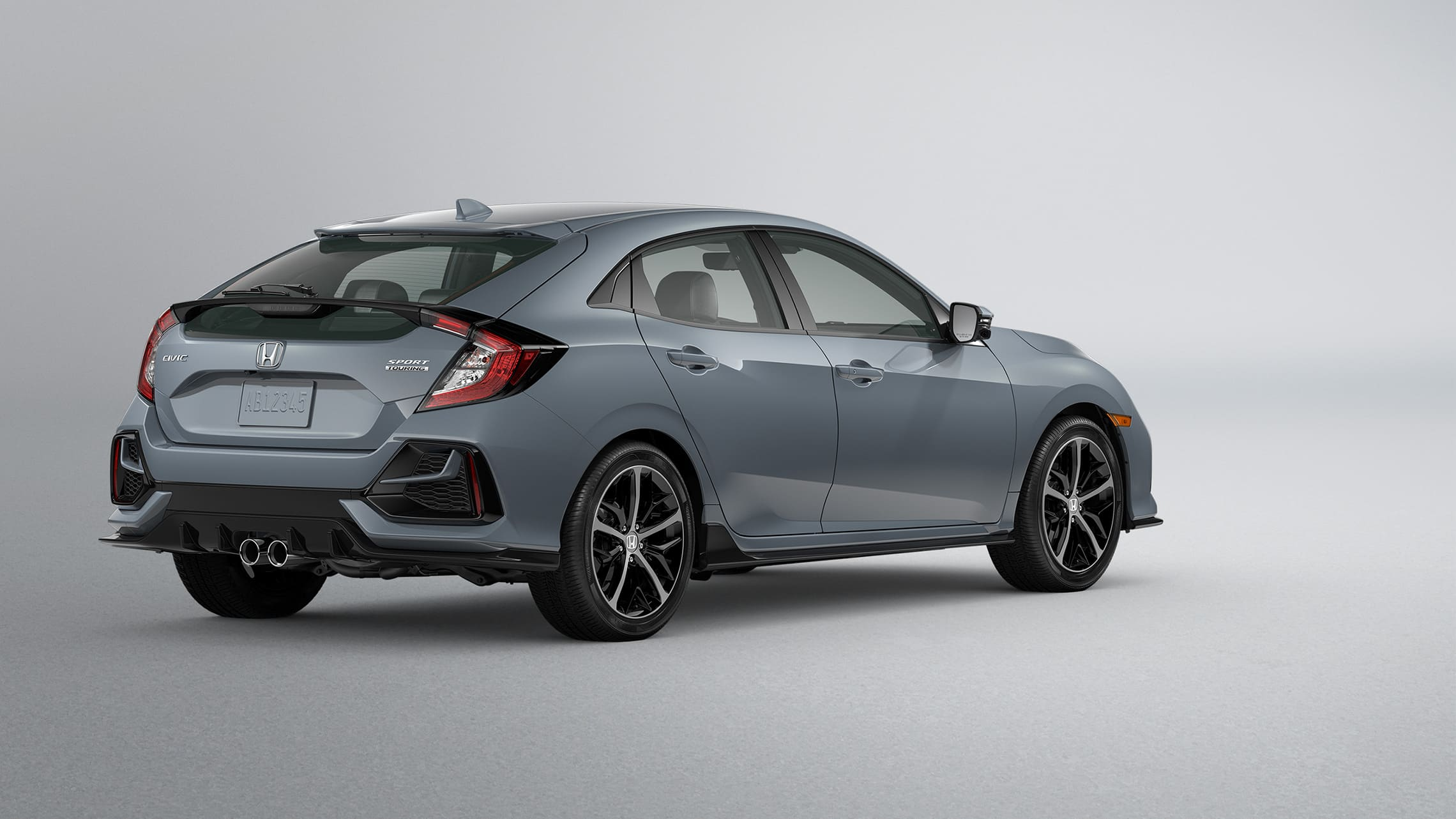 Rear 3/4 driver-side view of 2020 Honda Civic Sport Touring Hatchback in Sonic Gray Pearl.