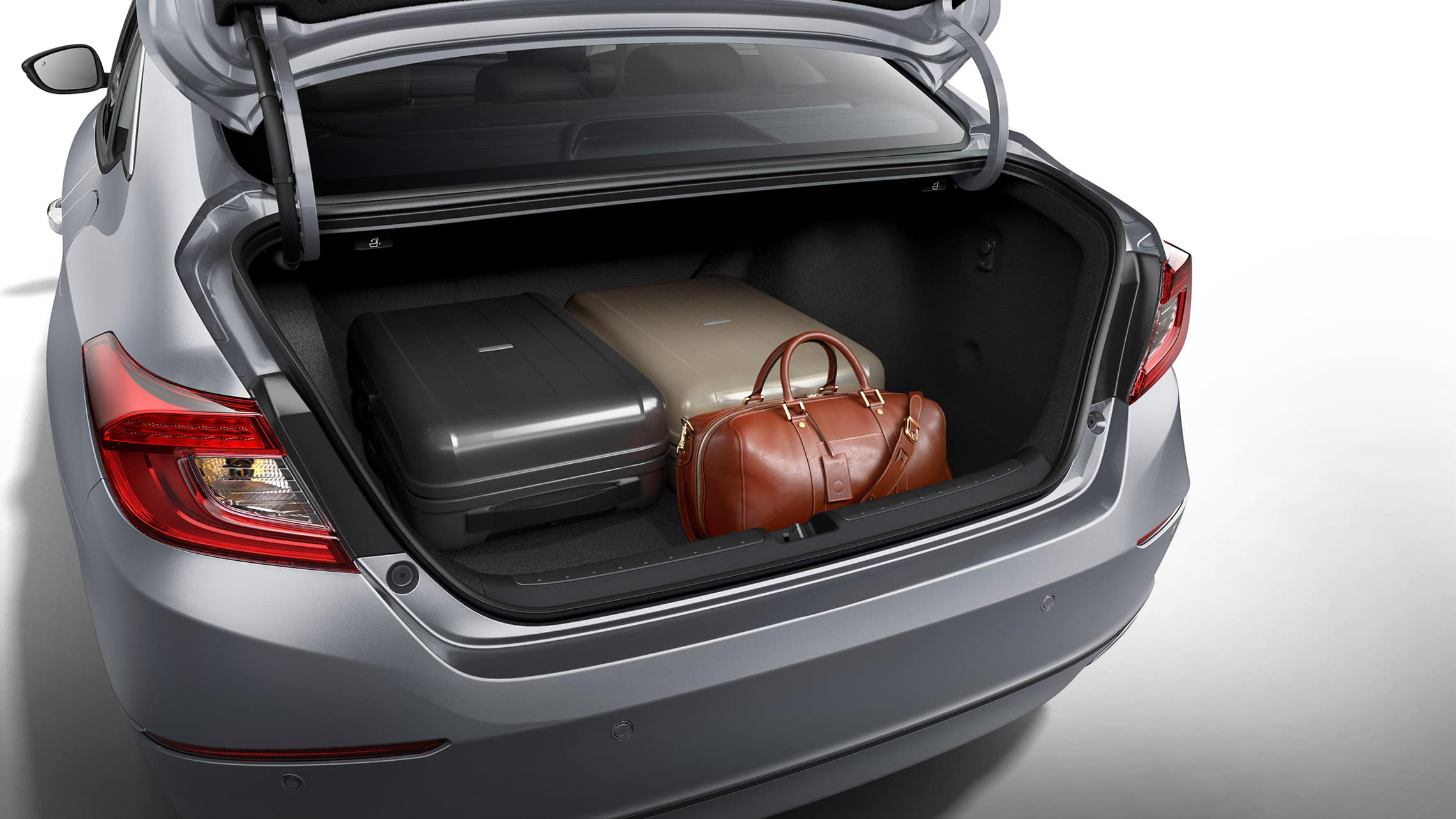 Rear view of the 2021 Accord Hybrid, shown in Lunar Silver Metallic, with the trunk open and with stored luggage displayed.